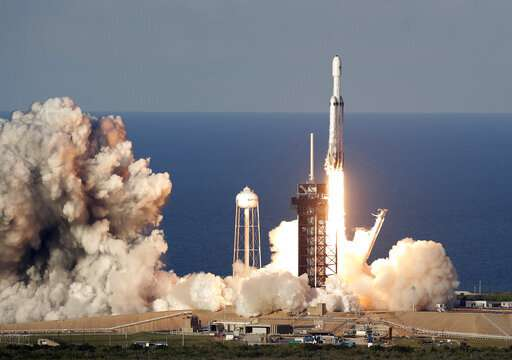 SpaceX launches mega rocket, lands all three boosters