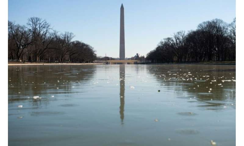 The Reflecting Pool on the National Mall in Washington is frozen as the region experiences frigid cold temperatures from a &quot