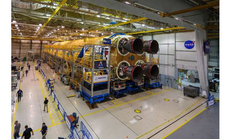 This NASA image obtained December 9, 2019 shows engineers and technicians as they attach the last of four RS-25 engines that wil