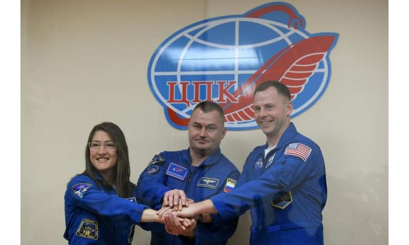 US astronauts Christina Hammock Koch (left) and Nick Hague (right) together with Russian colleague  Alexey Ovchinin are due to b
