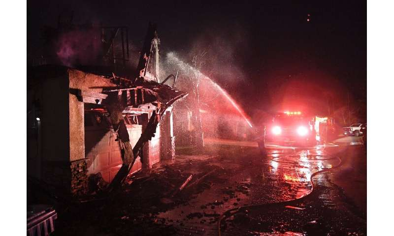 Firefighters hose down a burning house near Santa Clarita, California