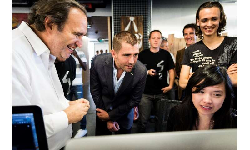 Facebook Chief Product Officer Chris Cox (C) listens to Xavier Niel (L), French businessman and founder of the French telecom an