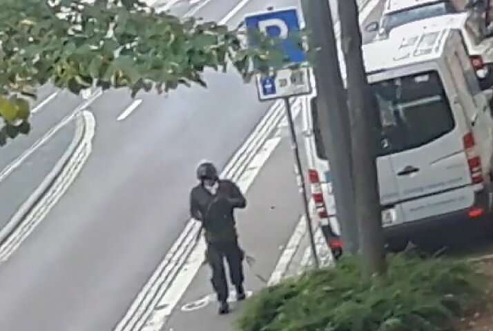 In this screenshot taken from a video by ATV-Studio Halle, a man walks with a gun in the streets of Halle an der Saale in easter