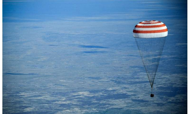 NASA astronaut Anne McClain, veteran cosmonaut Oleg Kononenko, and Canadian Space Agency record-holder David Saint-Jacques touch