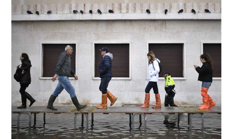 Officials erected a footbridge across a flooded street after the tide hit