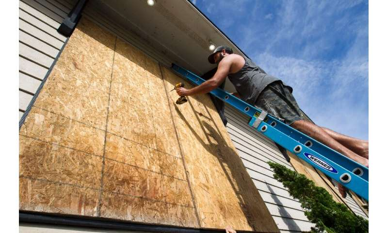Tayler Hofe boards up the windows of a surf shop in Avon, North Carolina, as Hurricane Dorian approaches