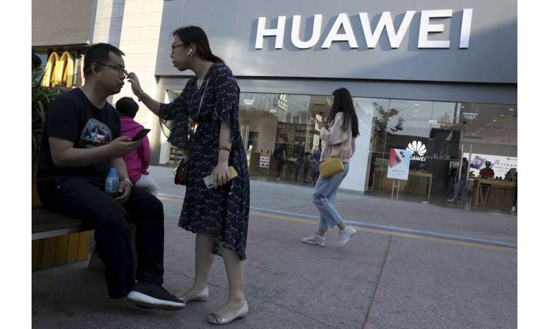 Tech group eases stance on Huawei as Beijing lashes back