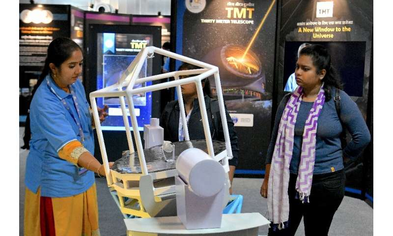 Visitors look at a scaled down model of the Thirty Meter Telescope (TMT) on display during a science exhibition in Bangalore in