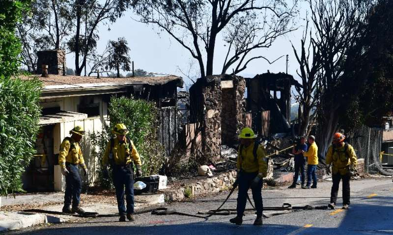 Firefighters gather their hoses near destroyed homes along North Tigertail Road near the Getty Center in Los Angeles on October