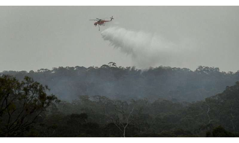 A helicopter dumps water on a bushfire in the outer suburbs of Melbourne
