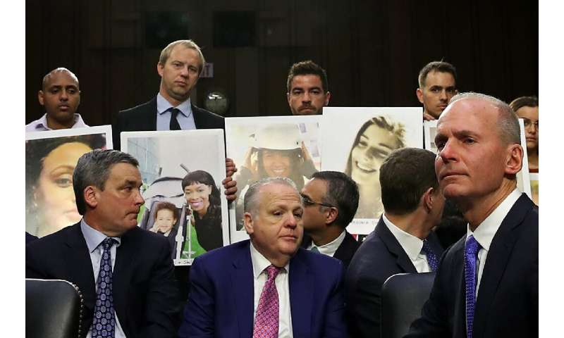 Family members of those who died aboard Ethiopian Airlines Flight 302 hold photographs of their loved ones as Dennis Muilenburg