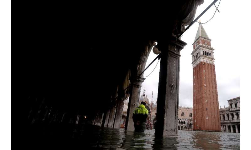 Schools reopened in Venice as shopkeepers with mops and buckets in hand tried to muck out the water and mud that flooded their s