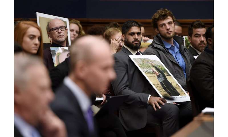 Family members of those who died aboard Ethiopian Airlines Flight 302 hold photographs of their loved ones during Muilenburg's t