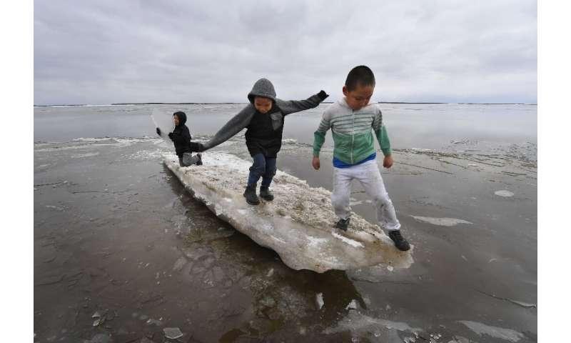 Schoolchildren play on melting ice at Yupik Eskimo village of Napakiak on the Yukon Delta in Alaska, where climate change threat
