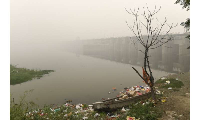 A boat is seen amidst heavy smog conditions surrounded by rubbish near a bridge along the Yamuna River in New Delhi