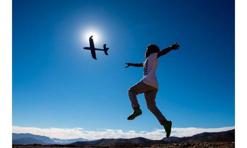 A boy plays with a toy glider on the eve of a solar eclipse, in La Higuera on the edge of the Atacama desert