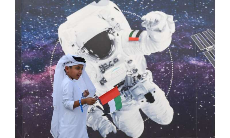 A boy waves the Emirati flag in front of a picture of an astronaut outside Mohammed Bin Rashid Space Centre in Dubai ahead of th