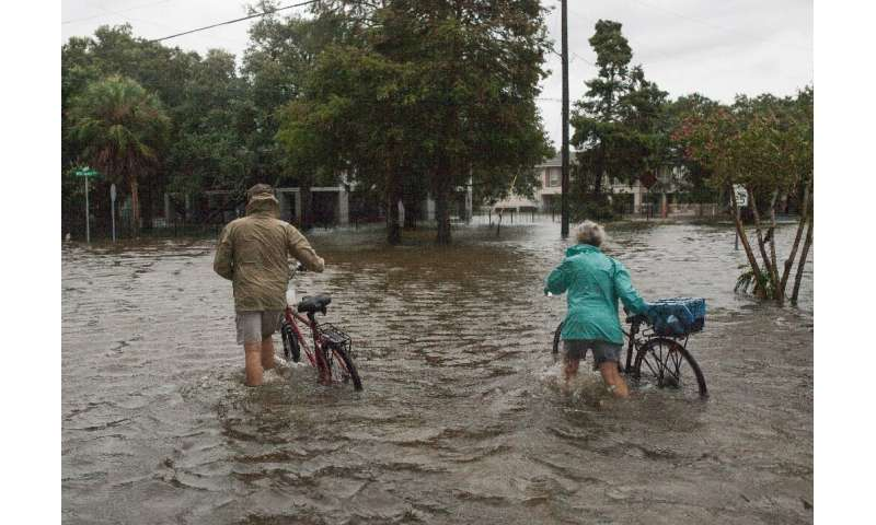 A couple walks their bikes through a flooded street after major storm Barry came ashore in Mandeville, Louisiana on July 14, 201