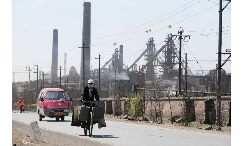 A cyclist is pictured in 2011 riding along a dusty road where dozens of factories process rare earths, iron and coal on the outs