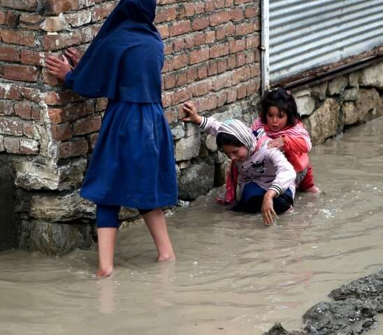 Afghan girls try to make their way home throught flooded streets in the Afghan capital, Kabul