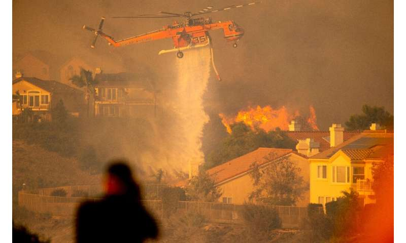 A helicopter drops water to help fight flames as the Saddleridge Fire in the Porter Ranch section of Los Angeles, California on