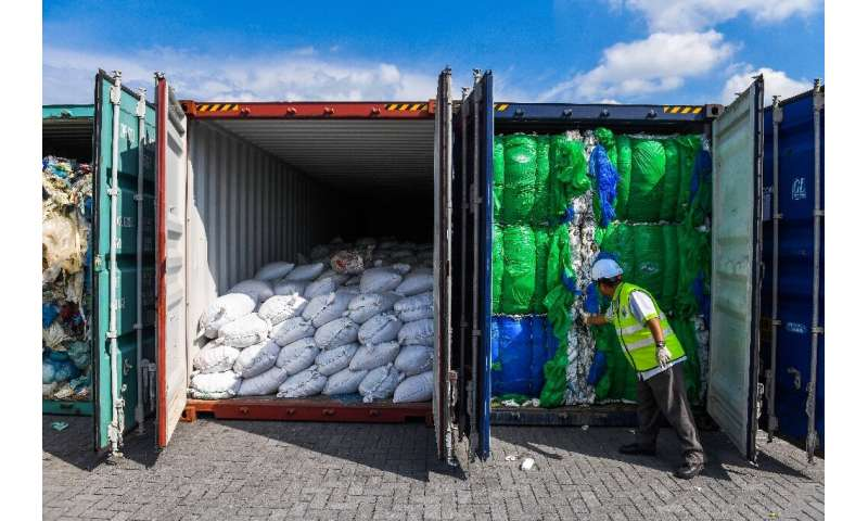 A Malaysian official inspects containers filled with plastic waste in Port Klang, west of Kuala Lumpur, in May 2019