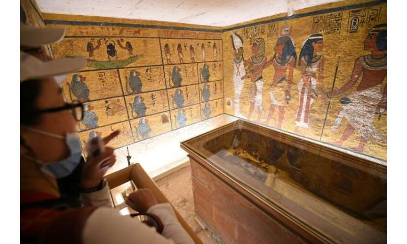 A man and a woman look at the golden sarcophagus of the 18th dynasty Pharaoh Tutankhamun, displayed in his burial chamber in the