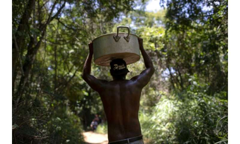 A member of the Pataxo Ha-ha-hae community carrying a cooking pan along a path through the forest