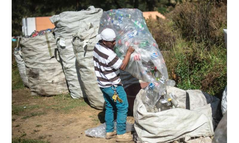 A Mexican worker loads bags with empty plastic bottles at a recycling center in Cheran
