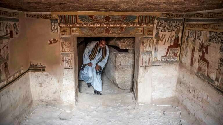 An antiquities security guard walks through the entrance to the newly discovered tomb from the Ptolemaic era (323-30 BC) near Ak
