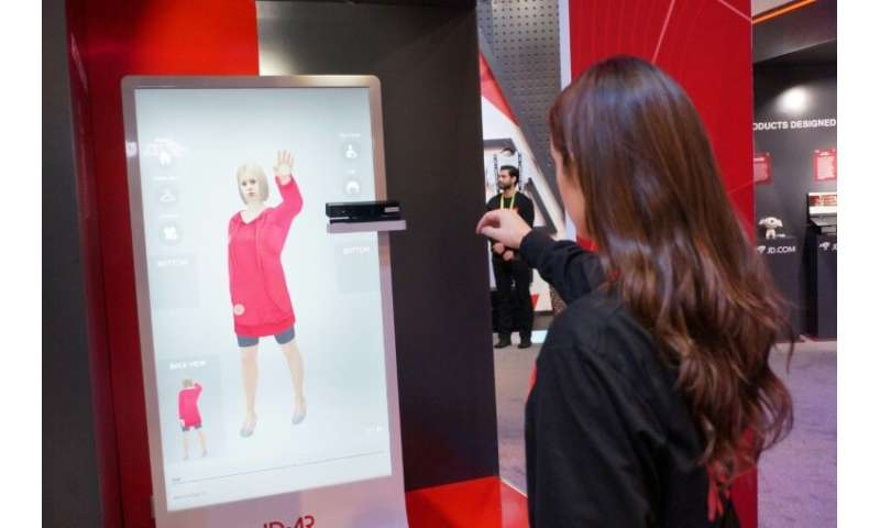 An employee of Chinese tech giant JD.com shows an augmented reality system that allows customers to virtually try on clothing at