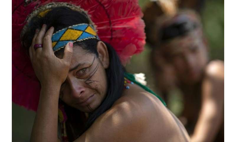 An indigenous woman of the Pataxo Ha-ha-hae community crying as she looks out over the Paraopeba river, filled with mud after a