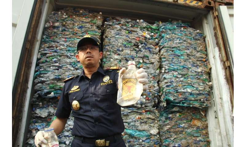 An Indonesian customs officer shows contaminated plastic waste from a container at Jakarta's international seaport