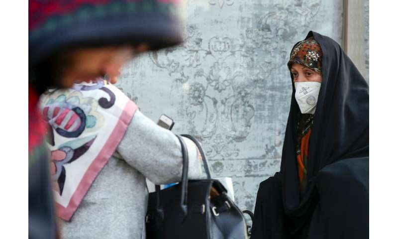 An Iranian woman wearing a breathing mask walks down a street as a blanket of smog covers Tehran