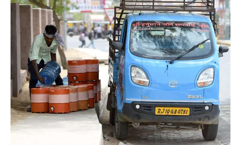 An man fills containers with water on a roadside in Churu, Rajasthan, which is sweltering under a heatwave