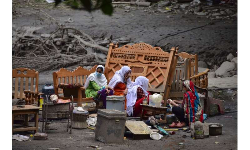 A Pakistani Kashmiri family gather around their belongings outside their damaged house following heavy monsoon rains in Neelum v