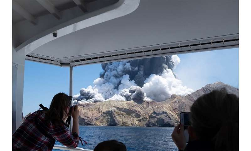 A photo courtesy of Michael Schade shows the volcano on New Zealand's White Island spewing steam and ash moments after it erupte