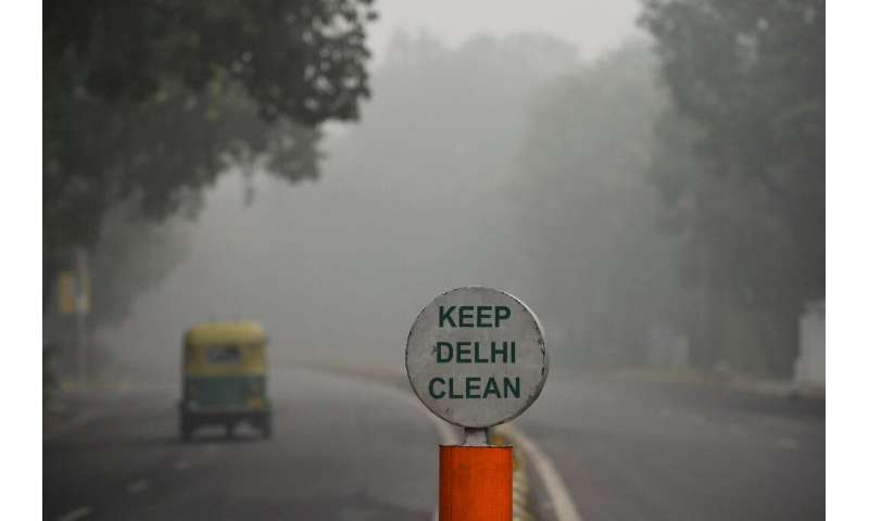 A rickshaw drives along a road under heavy smog conditions in New Delhi