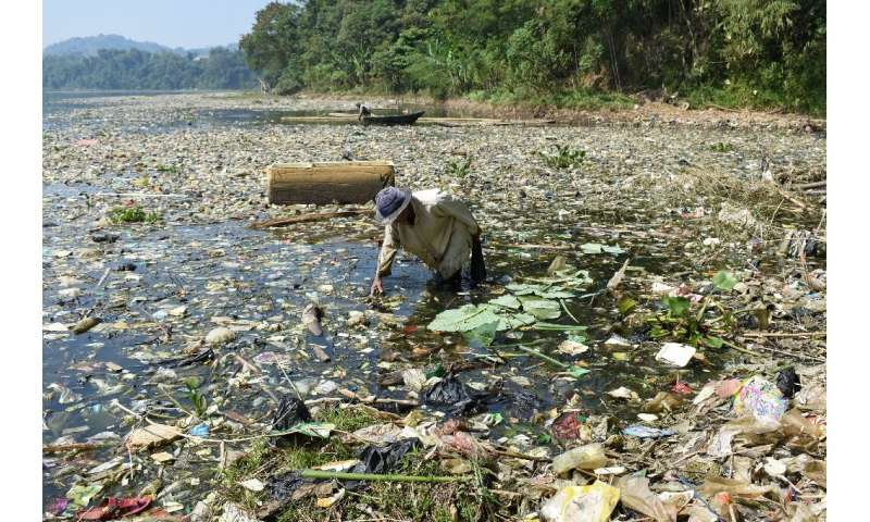 A scavenger collects plastic waste for recycling on the Citarum river, which is choked with garbage and industrial waste, in Ban