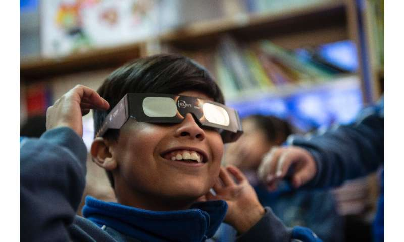 A schoolboy tries on special sunglasses at the Pedro Pablo Munoz school in La Higuera, Coquimbo Region, Chile, on the eve of a s