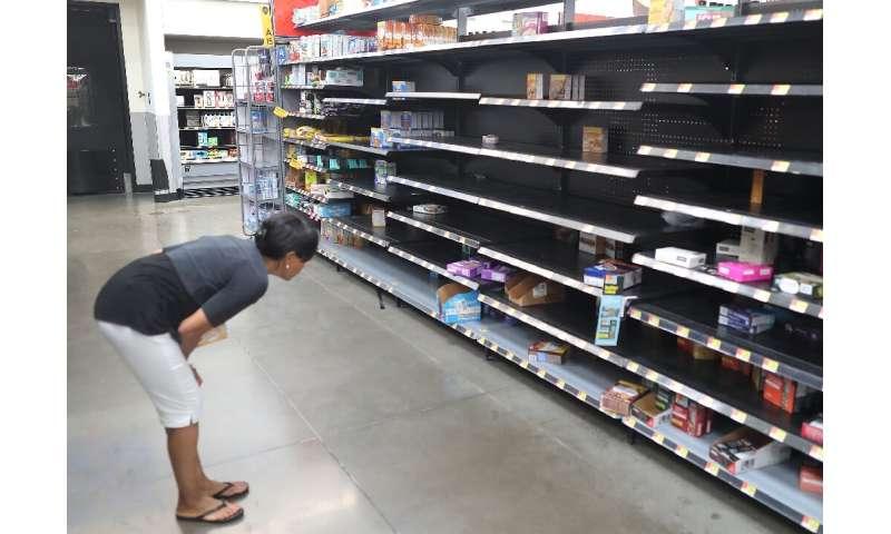 A shopper looks for items on nearly empty Walmart shelves in Boynton Beach ahead of the arrival of Hurricane Dorian
