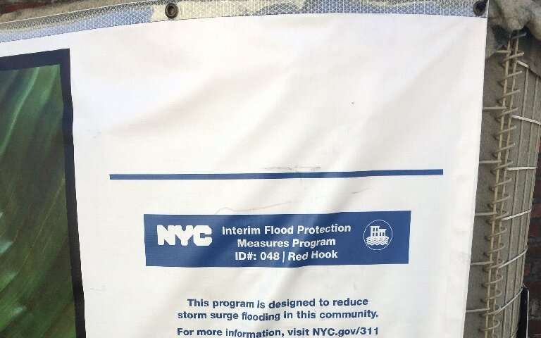 "A sign on a sandbag wall from the city of New York informs residents that ""Interim Flood Protection Measures Program"""