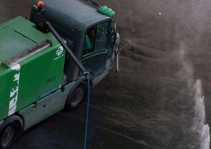 A street cleaner who sprays water to clean the sidewalk in Paris may also help cool down the temperature