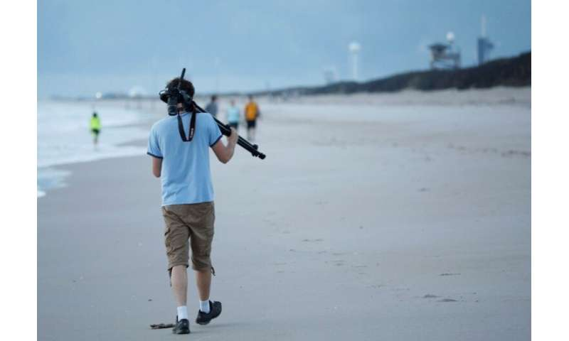 A visitor on a beach just north of the Kennedy Space Center in Florida, looking for a good vantage point to capture the launch o