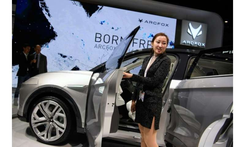 A visitor posing next to a car at the booth of Chinese carmaker Arcfox