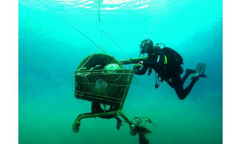 A volunteer for Greek environmental group Aegean Rebreath collects a trash-filled shopping cart from the sea on the Ionian islan