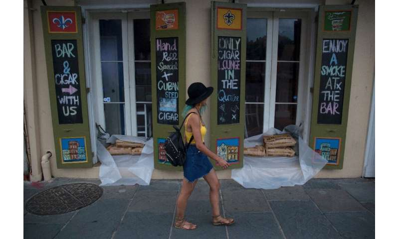 A woman walks past a cigar lounge and bar protected by sand bags in the French Quarter of New Orleans, in preparation for tropic