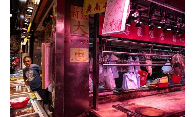 A worker looks out from a meat stall after fresh pork sold out in the Mong Kok district in Hong Kong
