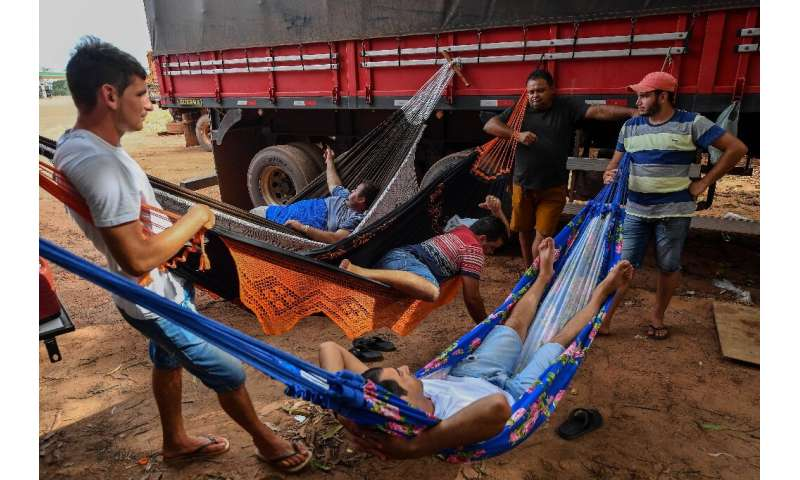 Brazilian trucker Erik Fransuer (L) speaks with other drivers resting on hammocks at a gas station in Ruropolis—he spends at lea