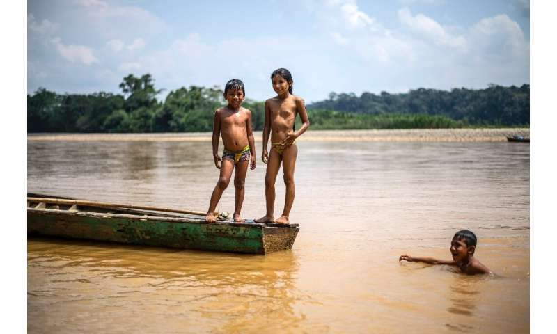 Children of the Arazaire indigenous group play in the Inambari river near Puerto Maldonado